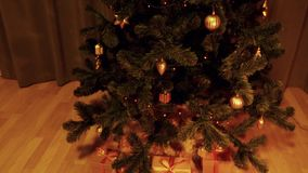 Crane tilt down indoors close up shot. Christmas tree with Fairy lights electric garland flashing. Gift boxes under. Green christmas tree. Golden bow on brown stock video footage