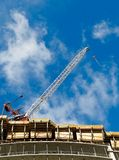 Crane on top of new condo tower Royalty Free Stock Images