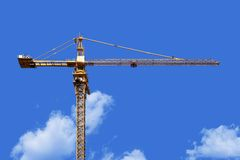 Crane tower. High crane tower on a clear blue sky with light clouds in a shiny day royalty free stock images