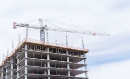 Crane towering over new building construction site Stock Photos