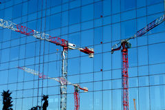 Crane towers reflected Stock Photography
