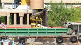Crane transfer load goods on conveyor belt into ship for transportation stock footage