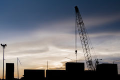 Crane transport container docks area silhouette with sunset background Royalty Free Stock Image