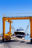 Crane travelift lifting a boat on blue sky day Stock Image