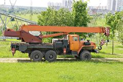 Crane truck. An orange crane truck standing in a city park Stock Photography