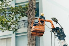 Free Crane Truck On Road For Group Of People Working In Saigon,Vietnam, Vietnamese Worker Work On Boom Lift To Cut Branch Of Tree For Royalty Free Stock Image - 193081466