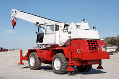 Crane Truck. Small red and white parked crane vehicle under blue sky. Horizontal Stock Image