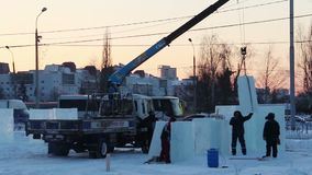 Crane unloads ice pieces for Ice town stock video