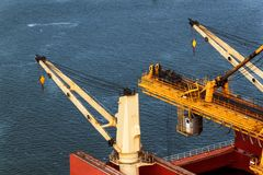 Crane unloads iron ore at the harbor. Trade in raw materials. Work at a port in the Baltic Sea. Crane unloads iron ore at the harbor. Trade in raw materials Royalty Free Stock Image