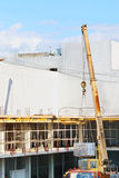 Crane unloads truck for building construction Stock Photo