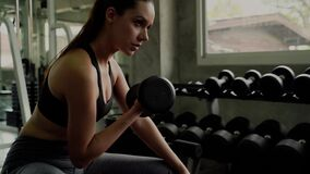 Crane video shot of beautiful woman lifting dumbbell in gym. She is strengthening arm muscles, side view.