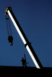Crane and worker. Silhouette of construction crane and worker upon a building roof Stock Images