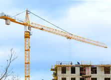 Crane and workers at construction of residental building. Stock Photography
