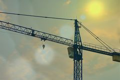 Crane working in construction area with sun flare royalty free stock photo