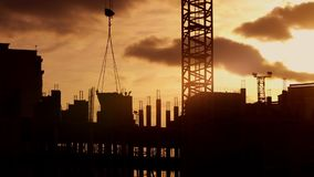 Crane working on construction elevate cement mixer, constructors on building. Silhouette of tower crane working on construction site elevate cement mixer stock footage