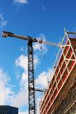 Crane working at an unfinished building with a bright blue sky royalty free stock images