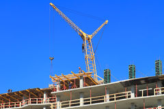The crane works on the top floors construction multi-storey at home Royalty Free Stock Photos