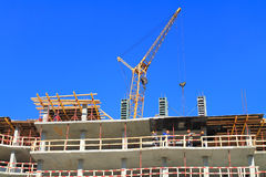 The crane works on the top floors construction multi-storey at home Royalty Free Stock Photo