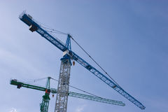 Cranes. Two cranes against a blue sky Royalty Free Stock Image