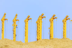 Cranes. Construction site with drilling rigs behind a sand hill Royalty Free Stock Photography