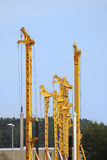 Cranes. Construction site with high yellow drilling rigs Royalty Free Stock Image