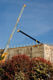 Cranes. Two telescoping mobile cranes towering over a building under construction royalty free stock photography