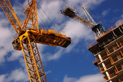 Cranes. Building under construction with two cranes royalty free stock image