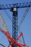 Cranes. Fragments of big construction cranes on a blue sky Royalty Free Stock Image