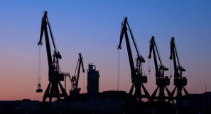 Cranes. Silhouettes of cranes from a port to the dusk Stock Image