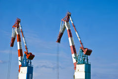Cranes. Heavy industrial cranes used to load and unload large cargo ships at a port Stock Photo