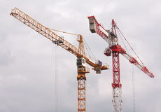 Cranes against cloudy sky. Two cranes against cloudy sky Royalty Free Stock Photography