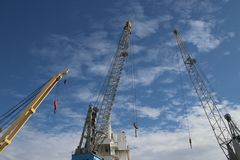 Cranes with blue sky and clouds in the port of Rotterdam, The Netherlands.  royalty free stock images
