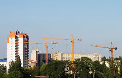 Cranes and buildin. G on a background blue sky Stock Photos