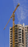 Cranes and building. High rise construction site with crane against a bright blue sky Royalty Free Stock Photo