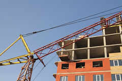 Cranes and building construction. A building under construction and a crane Stock Photos