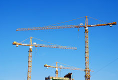 Cranes on building construction. Tree cranes and building construction on blue sky background, horizontal image Stock Image