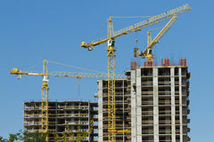 Cranes and building construction. On the blue sky Royalty Free Stock Photos