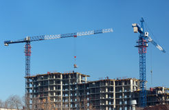 Cranes and building construction site against blue sky Stock Photography