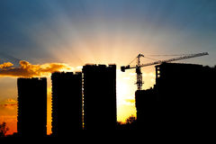 Cranes and building construction. Site against blue sunset sky Stock Photo