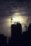 Cranes at building construction site. Cranes at industrial construction silhouettes Stock Photos