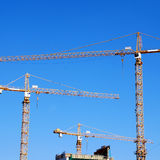 Cranes on building construction. Tree cranes and building construction on blue sky background, square image Stock Photo