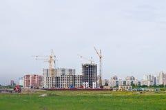 Cranes building modern blocks of flats. Panoramic view of cranes building modern houses royalty free stock photo