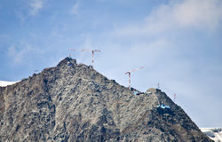 Cranes building on top of mountain Royalty Free Stock Photography