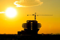 Cranes and buildings under construction against the setting sun Royalty Free Stock Photos
