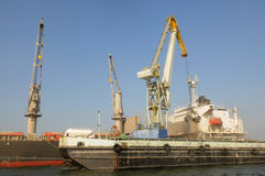 Cranes Loading a Cargo Ship with a Tanker Truck on Stock Photography