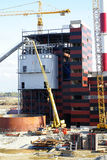 Cranes and chimney on construction site Stock Images