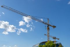 Cranes in the city. In front of a blue sky with some clouds royalty free stock image