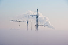 Cranes in clouds. Cranes and buildings in clouds Stock Image
