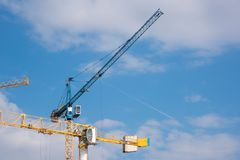 Cranes on a cloudy sky. Blue and yellow cranes on a cloudy sky Stock Image