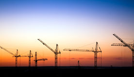 Cranes on a construction site against a sunset sky. Cranes silhouette on a construction site against a sunset sky Royalty Free Stock Photo